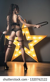 Beautiful woman in black lingerie and leather belt dominates the background of lamps and smoke