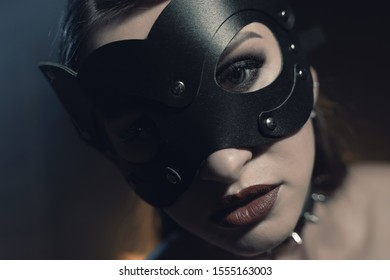 Beautiful woman in black lingerie and leather belt dominates in cat mask the background of lamps and smoke