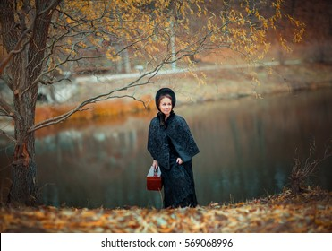 Beautiful woman in black long vintage dress and hood walking outside. Art work of romantic woman with a valise. Pretty tenderness model dreaming and looking afar. Woman traveling.