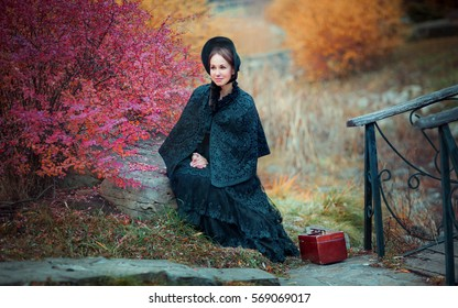 Beautiful woman in black long vintage dress and hood sitting on a stone outside. Art work of romantic woman with a valise. Pretty tenderness model dreaming and looking afar. Woman traveling.