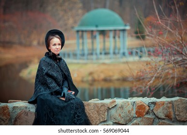 Beautiful woman in black long vintage dress and hood sitting on stone wall. Art work of romantic woman with a book. Pretty tenderness model dreaming and looking afar.
