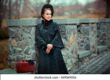Beautiful woman in black long vintage dress and hood standing near stone wall. Art work of romantic woman with a valise. Pretty tenderness model dreaming and looking afar. Woman traveling.
