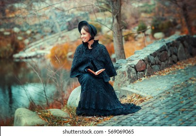 Beautiful woman in black long vintage dress and hood sitting on a stone outside and reading a book. Art work of romantic pretty tenderness model dreaming and looking afar.