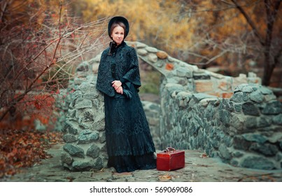 Beautiful woman in black long vintage dress and hood standing near stone wall. Art work of romantic woman with a valise. Pretty tenderness model dreaming and looking at camera. Woman traveling.