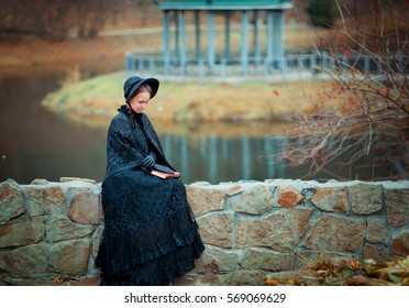 Beautiful woman in black long vintage dress and hood sitting on stone wall. Art work of romantic woman with a book. Pretty tenderness model dreaming and looking down.