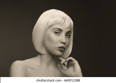 Beautiful woman with black nails wearing colorful short hair wig on black background. Sepia