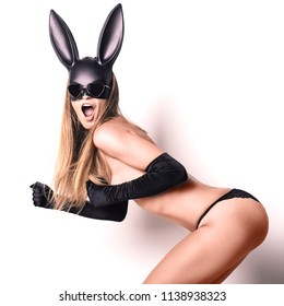 beautiful woman in black panties, satin gloves and a plastic rabbit mask stands sideways stands in the fighting stance opening her mouth in amazement simulates running on the spot