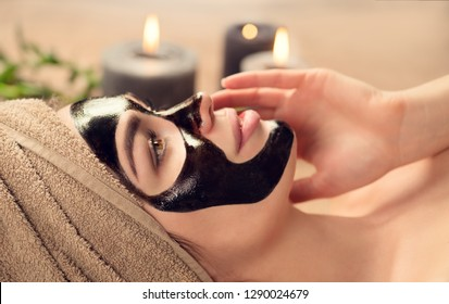 Beautiful woman with black purifying black mask on her face. Beauty model girl with black facial peel-off mask lying in spa salon. Skin care, acne treatment, cleansing   skin. Peel of charcoal mask