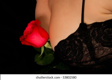 Beautiful woman in black satin and lace nightgown holding red rose between breasts.