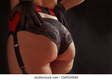 Beautiful woman in black stockings, erotic red stocking belt and lace panties on a black background with smoke close up