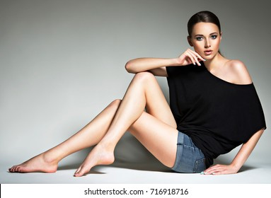 1ea2a92caa5 Beautiful woman in black t-shirt and blue jeans shorts. Fashion young girl  with
