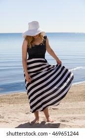Beautiful woman in a black and white sun-dress walking along the beach.