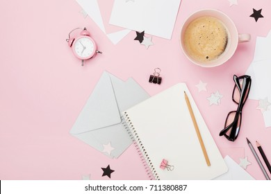 Beautiful woman blogger working desk with coffee, alarm, eyeglasses, pencil, envelope and empty notebook on pink pastel table top view. Flat lay. Cozy morning breakfast. Fashion color and style.