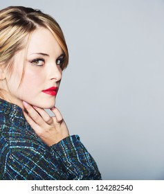 beautiful woman with blond hair in a bun wearing a tweed jacket and red lipstick on grey studio background