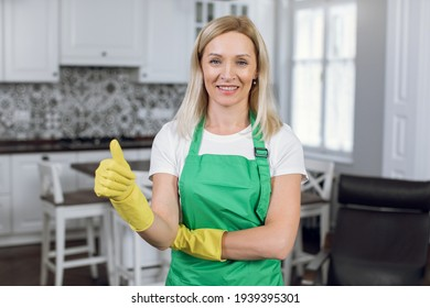 Beautiful woman with blond hair showing thumb up while smiling and looking at camera. Female housekeeper wearing green apron and yellow rubber gloves.