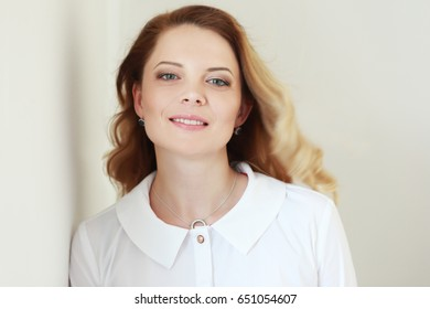 beautiful woman with blond hair in white shirt, smiling on camera