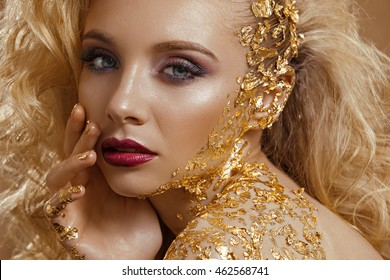 A beautiful woman , blond wavy hair , make-up , the color of gold , gold jewelry , beauty fashion model clean skin close-up portrait . Body gold pattern. Photographed in studio on a gold background