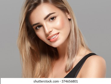 Beautiful woman blonde hair portrait close up studio on gray