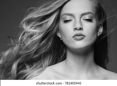 Beautiful woman with blonde long hair over gray background black and white
