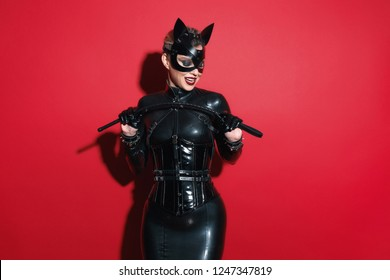 Beautiful woman blonde model vamp mistress dominatrix bdsm woman in glamour latex dress, corset, cat mask and black leather fetish harness posing in sex shop red room