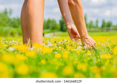 Beautiful woman in a blooming field collects bouquet of yellow flowers in summer day.