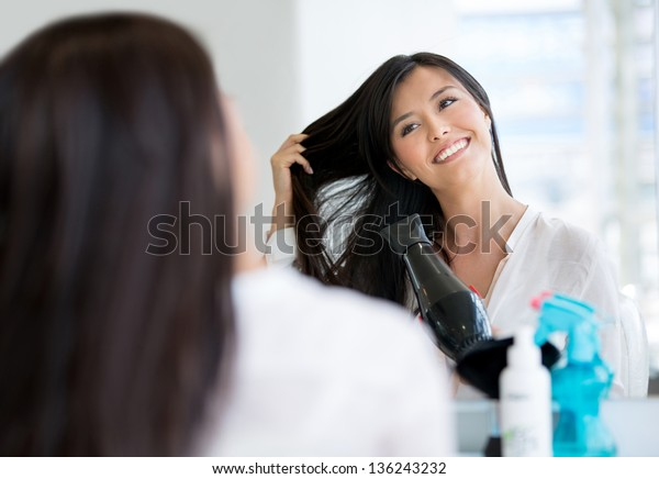 Beautiful woman blow drying her hair at the salon