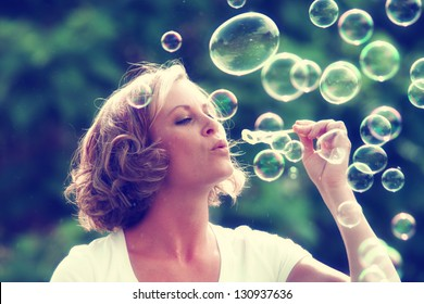 a beautiful woman blowing bubbles toned with a retro vintage instagram filter