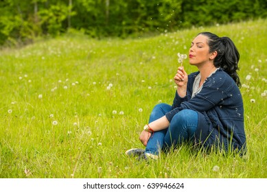 Beautiful woman blowing dandelions seeds and sitting on grass in nature