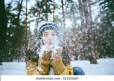 Beautiful Woman Blowing Snow. Magic snowfall effect.