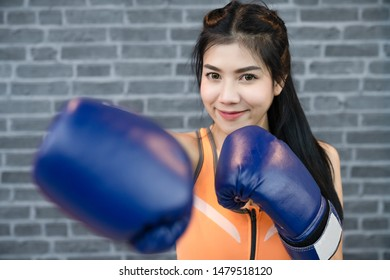 beautiful woman with the blue boxing gloves. Woman boxer training hard , concept about challenge sport