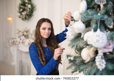 Beautiful woman in blue dress decorating the christmas tree.