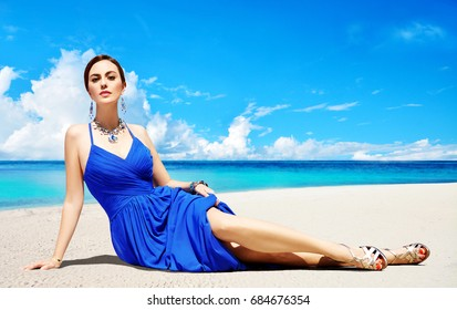 Beautiful woman with blue dress, earrings and necklace, and gold sandal shoes laying on the beach sand. Summer fashion image.
