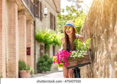 Beautiful woman in blue dress and hat riding retro bicycle full of flowers in the old italian town