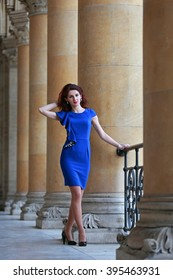 Beautiful woman with blue dress and high heels standing in arcades