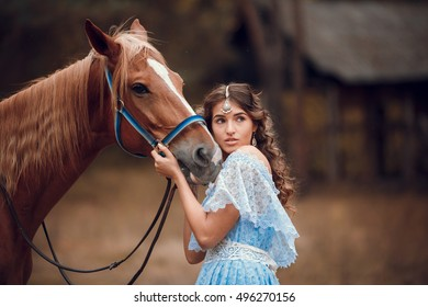 Beautiful woman in a blue dress hugging a horse. Retro style.