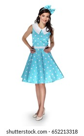 Beautiful woman in blue dress with polka dots with bow on head smiling looking at camera standing on white background