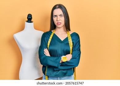 Beautiful woman with blue eyes standing by manikin with crossed arms skeptic and nervous, frowning upset because of problem. negative person.