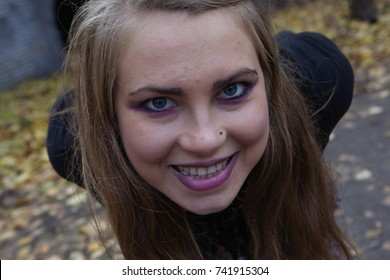 Beautiful woman with blue eyes standing in a park in autumn