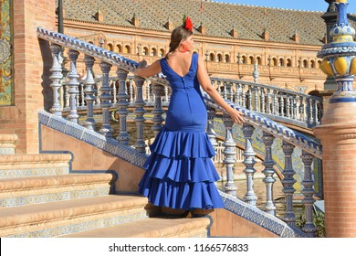 the beautiful woman with the blue flamenco dress on the stairs