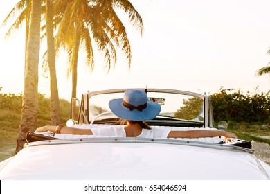 Beautiful woman in blue hat and white retro cabriolet on the beach