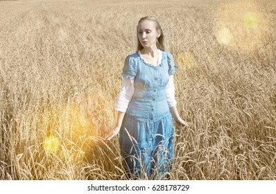 The beautiful woman in a blue long dress in the field of ripe cereals