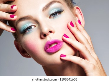 Beautiful woman  with blue makeup of eyes and pink nails. Glamour fashion model.  Fashion portrait of a attractive woman with bright makeup.  Gorgeous girl.