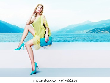 Beautiful woman with blue purse and shoes sitting on the lake side. Summer fashion image. Italy lake Como.