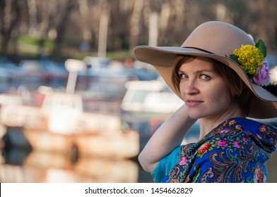 Beautiful woman with blue Russian scarf walking and posing next to river with boats