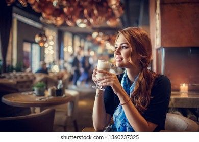 Beautiful woman in a blue shawl drinking coffee sitting in a cafe