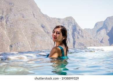 Beautiful woman in blue swimsuit in the water in front of huge mountains.