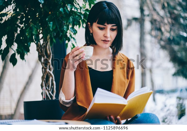 Beautiful woman with bob haircut reading romantic literature during tea break at cafeteria with loft interior, young charming hipster girl spending free time for autodidact with books on leisure