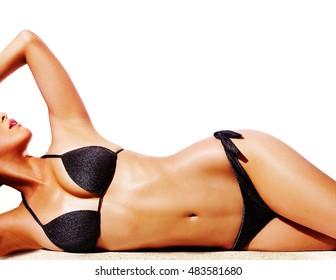 Beautiful woman body with black bikini swimwear isolated on white. Perfect body skin with sun tanned shine.