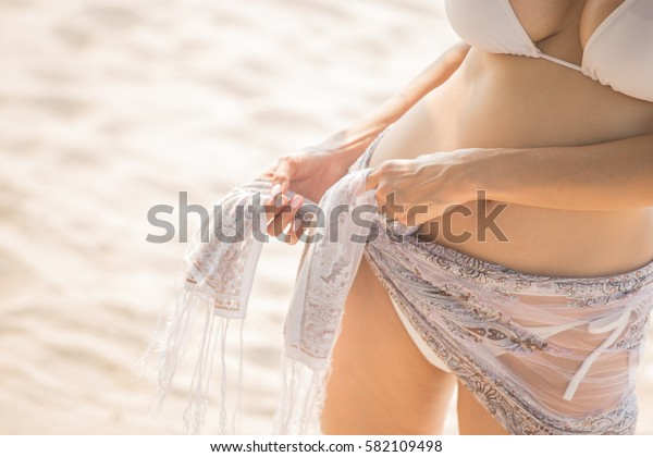 Beautiful woman body posing at the summer sand beach. Outdoor summer portrait.