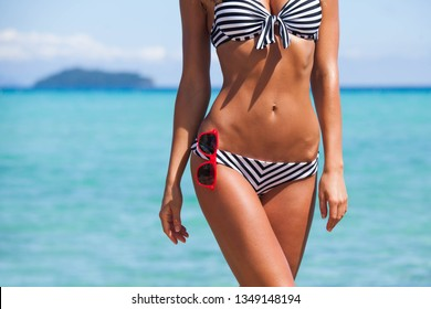 Beautiful woman body with striped bikini and sunglasses over tropical sea background